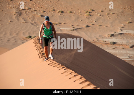 Hiking along the pristine ridge of a huge red sand dune in the Namibia desert - Stock Photo