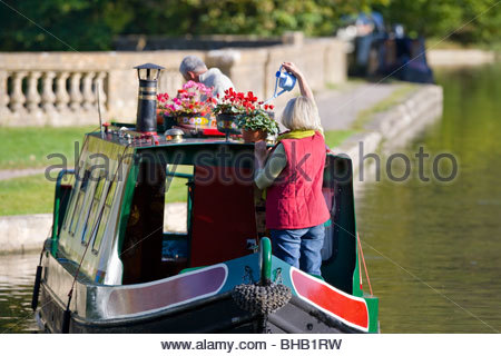 Woman watering potted flowers on narrow boat in canal - Stock Photo