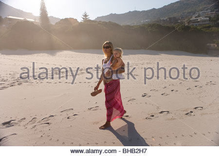 Mother walking on beach with baby girl (12-15 months), (lens flare) - Stock Photo