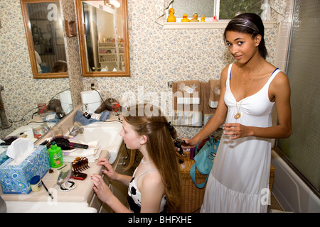 Preparing for their Formal Dance,  African American girl doing her friends hair in the bathroom, on her knees. - Stock Photo