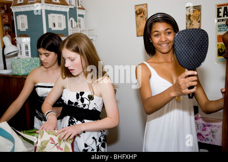 Preparing for their Formal Dance, five multi-ethnic girls putting on make up and doing their hair in the bathroom. - Stock Photo