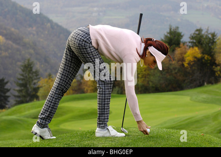 A golf player putting a golf ball on the lawn, Golf court Kastelruth Alpe di Siusi, Sciliar, South Tyrol, Italy, - Stock Photo
