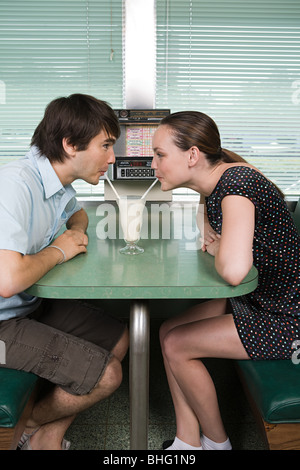 Young couple drinking a milkshake - Stock Photo