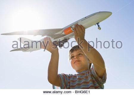 Little boy holding toy plane - Stockfoto
