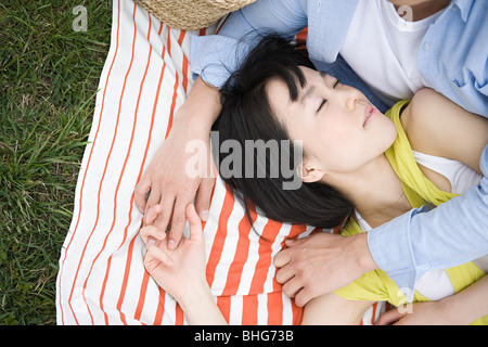 Young couple sleeping on blanket - Stock Photo