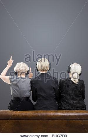 Rear view of senior women wearing headphones - Stock Photo