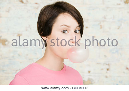 Young woman blowing bubble gum - Stock Photo