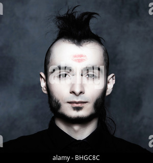 studio portrait of a young stylish man with a Lipstick Kiss mark on his forehead - Stockfoto