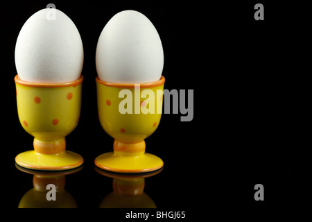 chicken eggs in dotted eggcups on reflecting black background - Stock Photo