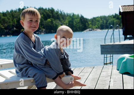 Brother and sister on a jetty, Stockholm archipelago, Sweden. - Stock Photo