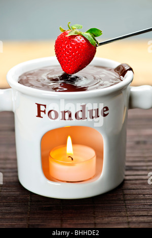 Strawberry dipped in delicious melted chocolate fondue - Stock Photo