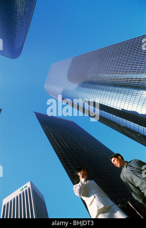 Businessman and woman under downtown Los Angeles Civic Center skyscrapers - Stock Photo