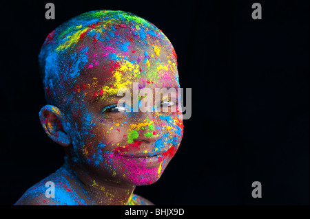 Happy young Indian boy covered in coloured powder pigment against a black background - Stock Photo
