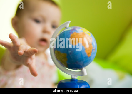 Infant girl reaching for toy globe - Stock Photo