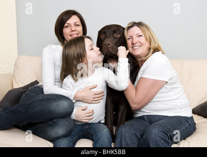 Shot of Three Generations of a Family Laughing with their Dog - Stock Photo
