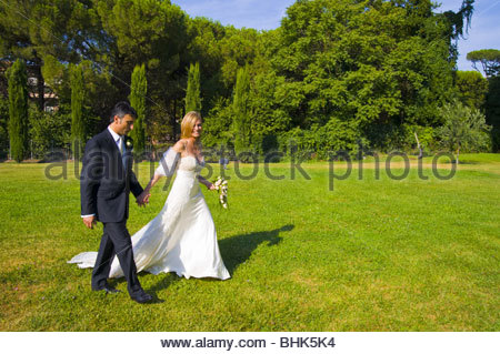 Bride and groom walking hand in hand through a park - Stock Photo