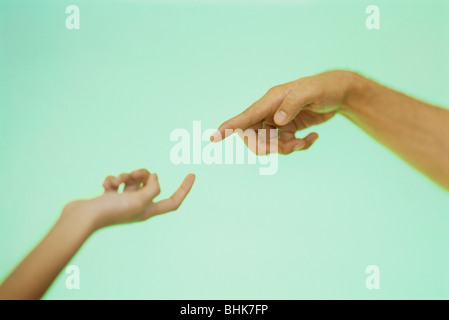 Two hands reaching toward each other with index fingers extended - Stockfoto