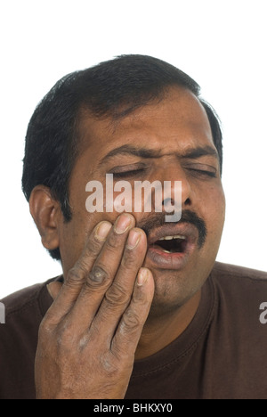Indian man hand over mouth with tooth pain - Stock Photo