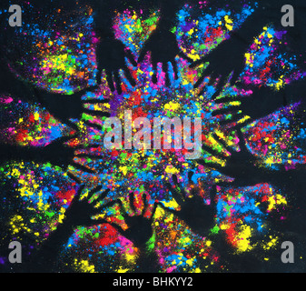 Multicoloured powder hand prints in a circular pattern on black - Stock Photo