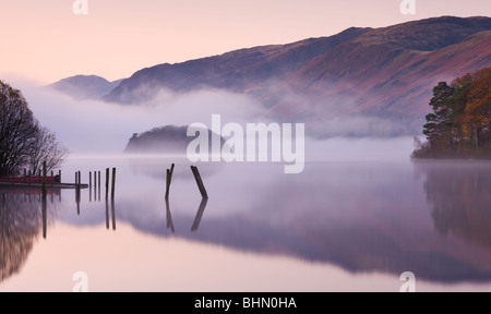 Mist surrounds a peaceful Derwent Water at dawn, Lake District National Park, Cumbria, England. Autumn (November) - Stock Photo