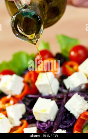 Close up macro photograph of olive oil dressing being poured onto a fresh salad - Stock Photo