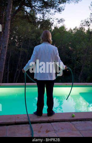 looking at the rear of a suited blond man standing by the side of swimming pool with a hose pipe in his hands - Stock Photo