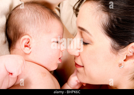 Face of baby and mother together, infant expressing anger and holding fist ready to punch. - Stockfoto
