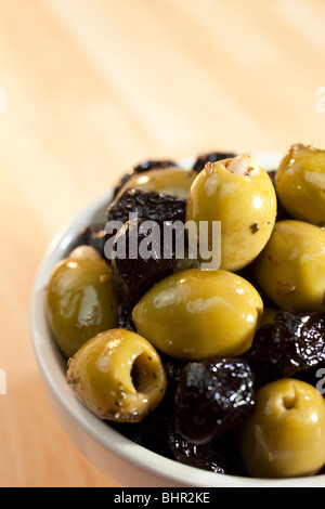 Close up macro photograph of a bowl of stuffed green and black Italian olives - Stock Photo