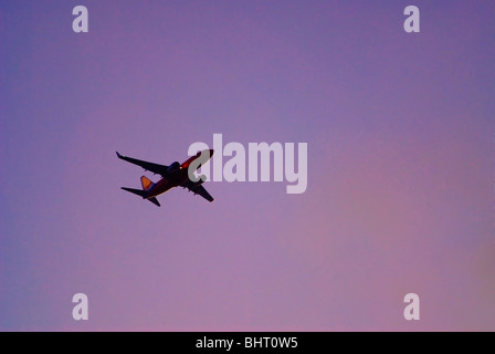 Airliner flying in sunset sky - Stock Photo
