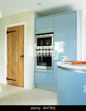 Pale blue fitted units in country kitchen with pale wood for Tall fitted kitchen unit