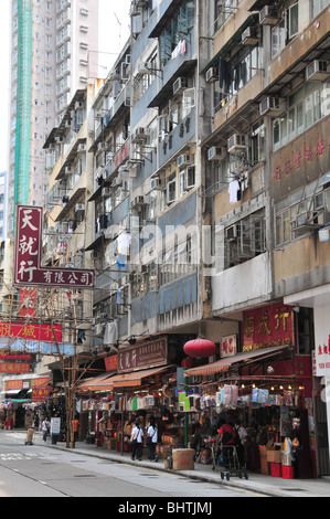 Apartments, clothes hanging from windows, above shops selling lanterns, clothes, household items. Queen's Road West, - Stock Photo