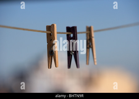 three clothes pegs hanging on a washing line against a bright blue sky over the city - Stock Photo