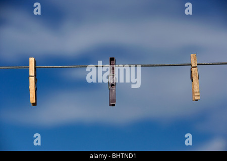 three clothes pegs hanging on a washing line against a bright blue sky - Stock Photo