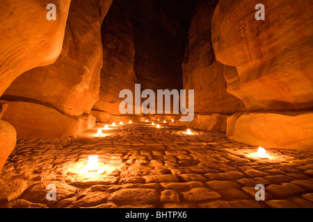 The Al-Siq Canyon leading to the Treasury lit up by candles for Petra by night in Wadi Musa, Jordan. - Stock Photo