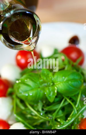 Close up macro photograph of olive oil dressing being poured onto fresh rocket and basil salad with tomatoes & balsamic - Stock Photo