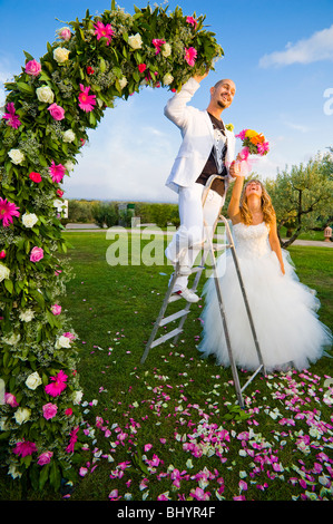 Bride and groom on ladder near flower arch - Stock Photo