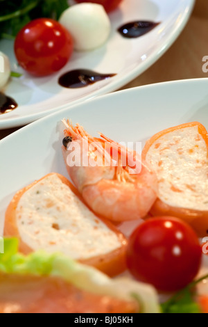 Shrimp and salmon mousse alongside tomato, mozzarella and rocket salad with olive oil and balsamic vinegar dressing - Stock Photo