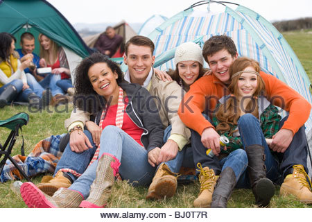 Happy couples camping in tent and attending outdoor festival - Stock Photo