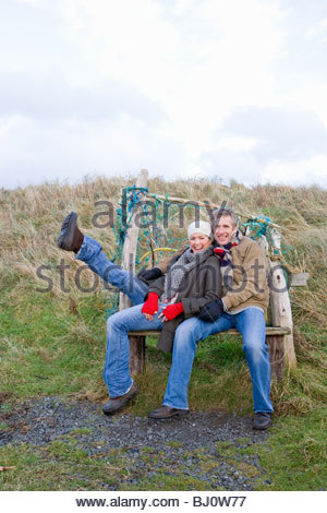 Couple sitting on bench enjoying outdoors in winter - Stock Photo