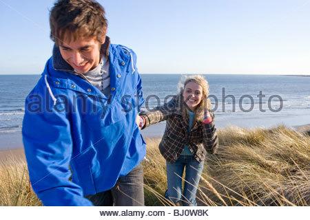 Couple walking on sand dune near ocean - Stock Photo