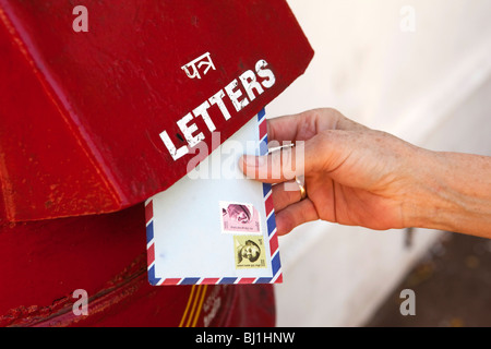 India, Kerala, Kochi, Fort Cochin, woman's hand posting air mail letter in post box - Stockfoto