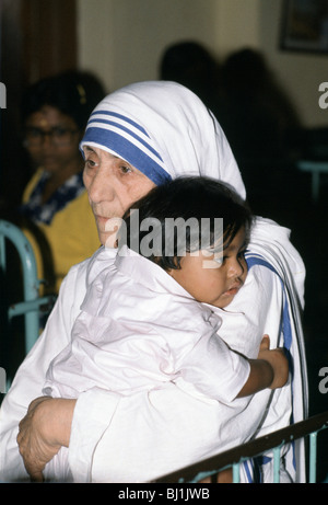 Mother Teresa of Calcutta hugs a child at her mission to aid poor and starving people, Calcutta, India - Stockfoto