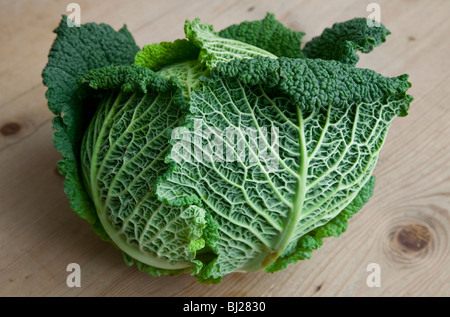 CLOSE UP OF SAVOY CABBAGE ON WOODEN TABLE - Stock Photo