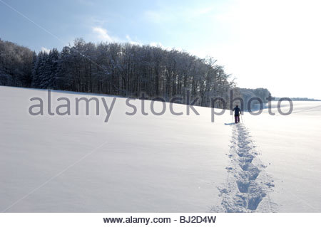 A snowshoe hiker leaves deep traces in the snow at the Swabian Alb. Böhringen-Römerstein; Häsel, Germany; Baden - Stock Photo