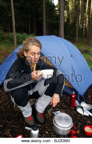 Hike in the eastern Harz from Wernigerode to Ilfeld. Woman and man having breakfast in front of tent campsite Am - Stock Photo