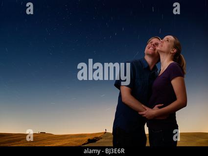 couple watching the starry night sky - Stock Photo