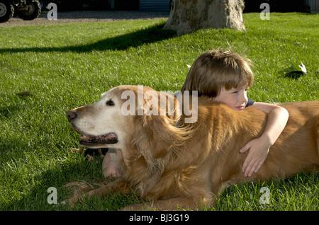 Boy rests on dog - Stock Photo