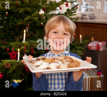 boy holding plate of homemade biscuits - Stock Photo