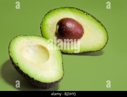 Hass variety avocado pear sliced into two halves against a green background. - Stock Photo