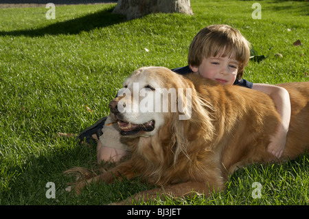 Boy and dog resting in the grass - Stock Photo